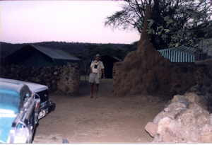 Dr. Harper is dwarfed by the tall termite mound at the entrance to the tent camp
